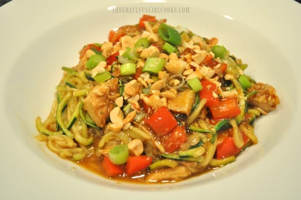 Bowl of Kung Pao Zoodles garnished with chopped peanuts and green onions.