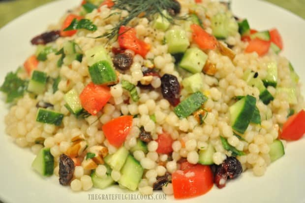 Close up photo of lemon herb couscous salad in white bowl.