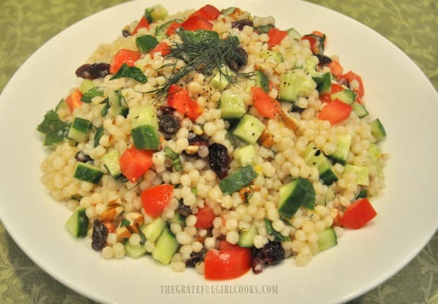 Lemon herb couscous salad in white bowl, with fresh dill garnish on top.