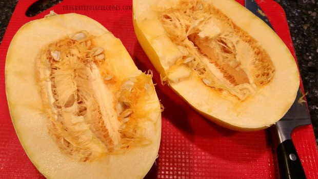 Spaghetti squash is cut in half lengthwise to remove seeds.