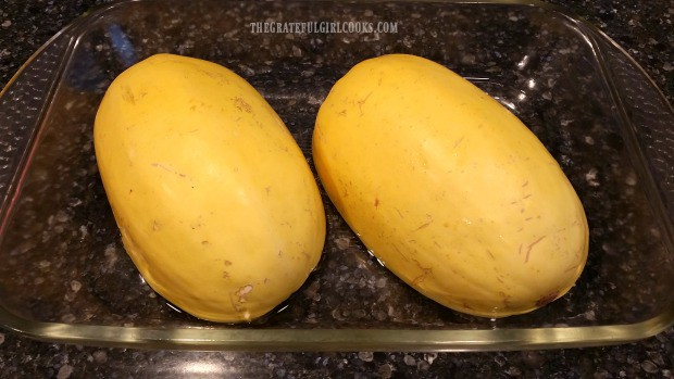 De-seeded spaghetti squash halves are placed cut side down in baking pan with water.