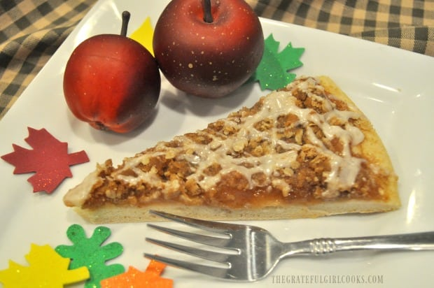 A slice of apple pie dessert pizza on white plate, with apple and leaf decorations.