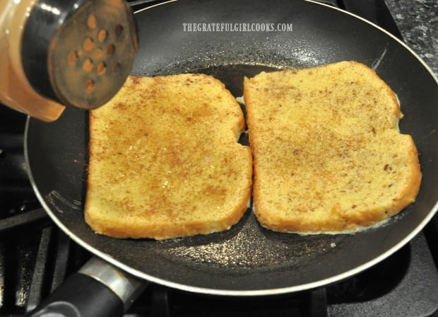 Classic french toast is placed into hot skillet to cook, and sprinkled with cinnamon.