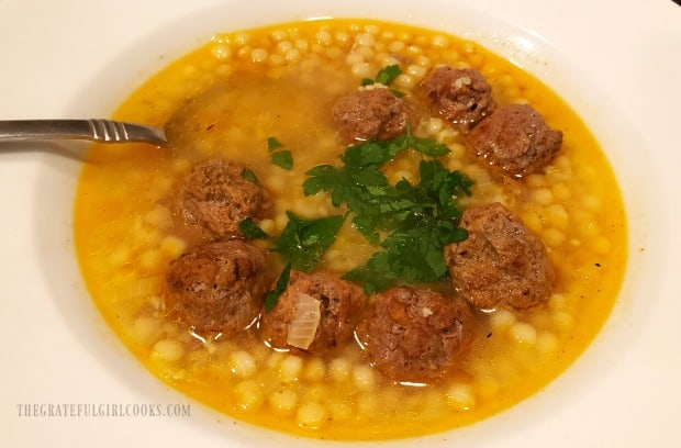 Moroccan meatball couscous soup, served in white bowl, with fresh parsley garnish.