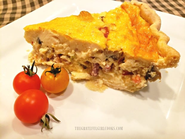 A slice of Southwestern bacon quiche, on a white plate, with a few cherry tomatoes.