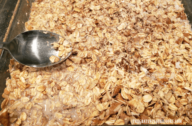 Milk mixture is added to blueberry baked oatmeal dish, and oats are pressed down into liquid.