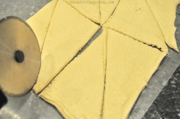 Slicing crescent roll dough into triangles to make the crescent roll coffeecake.