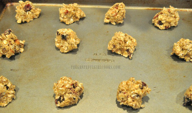 Oatmeal cranberry pecan cookie dough is placed in spoonfuls on baking sheet.