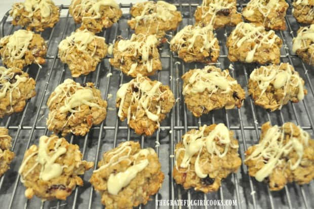 Oatmeal cranberry pecan cookies, drizzled with white chocolate, on wire rack after baking.