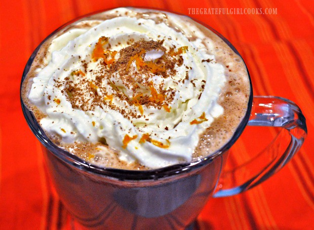 Whipped cream, orange zest, and zested chocolate top a mug of Valencia orange hot chocolate.
