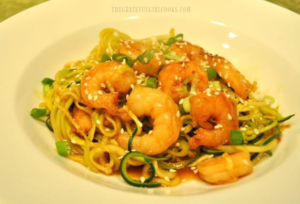 Sweet chili sesame shrimp zoodles, served with green onion garnish, in white bowl.