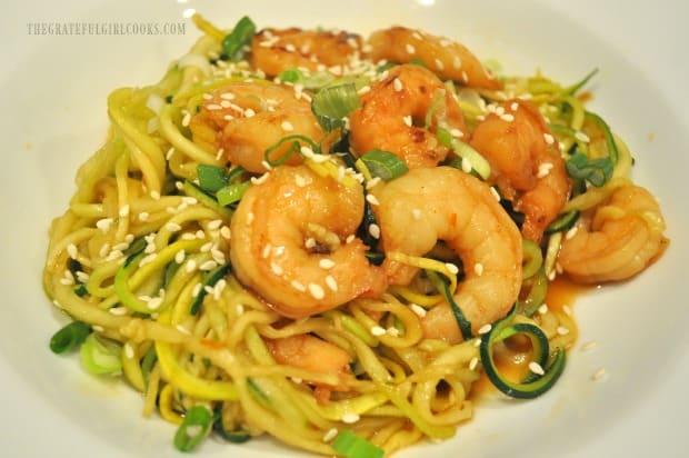 Sesame seeds and green onions garnish the sweet chili sesame shrimp zoodles.