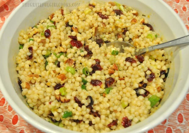 The cranberry orange Israeli couscous is served, in a white bowl.