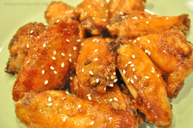 The baked Asian chicken wings are served, garnished with sesame seeds.