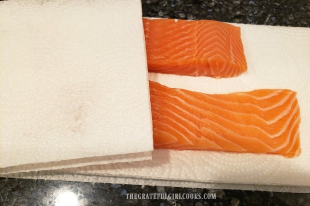 Salmon fillets are blotted dry with paper towels before cooking.