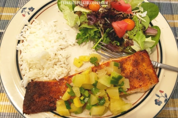 Broiled salmon with pineapple salsa, served on plate with rice and green salad.