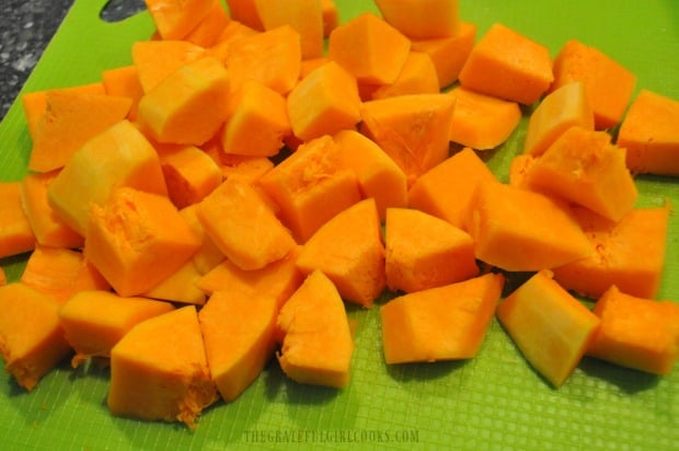 The butternut squash is peeled, seeded, then cut into bite sized pieces before baking.