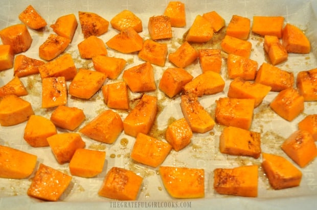 The pieces of maple cinnamon butternut squash are placed on parchment paper to bake.