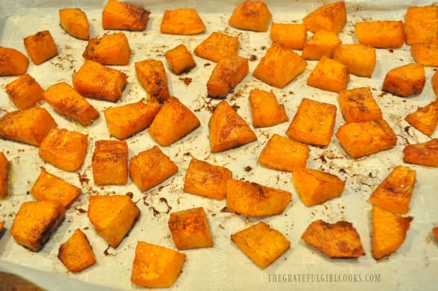 Halfway through baking time, maple cinnamon butternut squash is turned to other side to finish cooking.