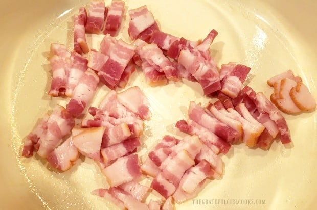 Thinly sliced bacon is cooked to add to fried cabbage.