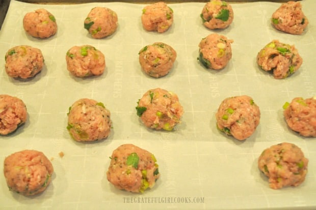 The Thai turkey meatballs on parchment paper lined baking sheet before baking.