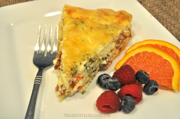 One slice of bacon broccoli quiche, with fresh fruit on the side.