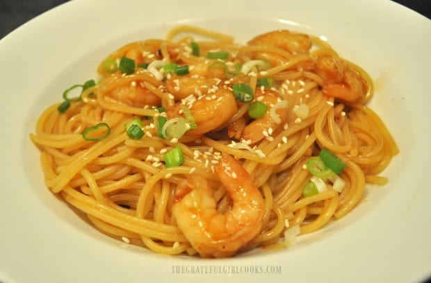 The sweet chili shrimp pasta is served, topped with sesame seeds and green onions.
