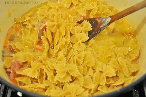 Bow tie pasta noodles are added, to cook in the liquid in saucepan.