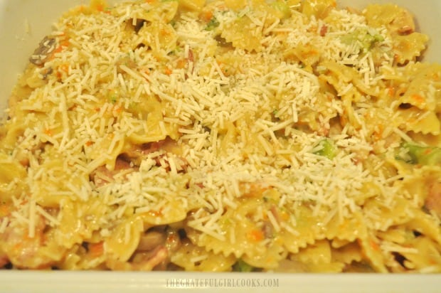 Bacon broccoli pasta casserole is placed in baking dish and topped with Parmesan to bake.