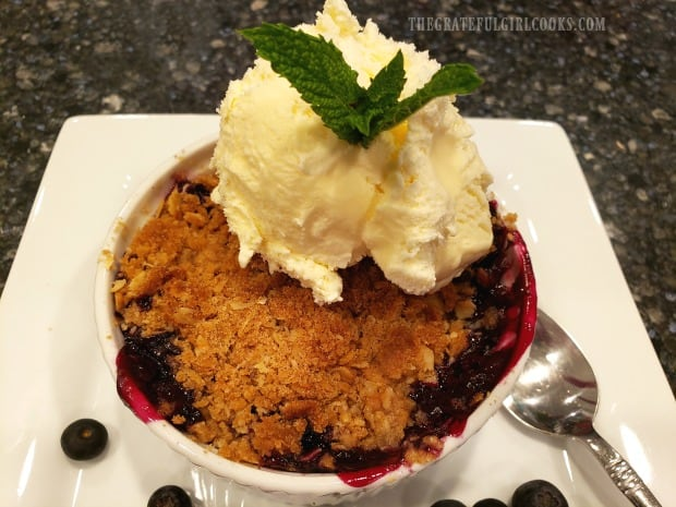 Blueberry Crumble is served with vanilla ice cream and a mint leaf on top!