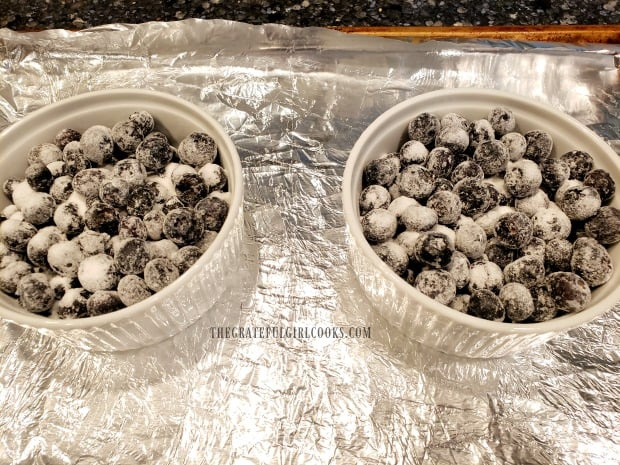 Two ramekins are filled with the sugar coated fresh blueberries.