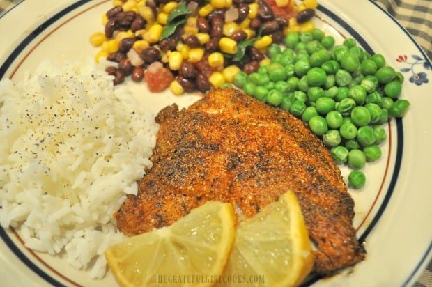 Lemon wedges garnish the finished cornmeal spice-crusted rockfish, served with rice and veggies.