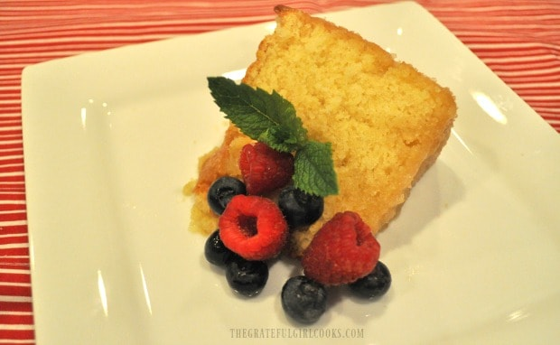 A slice of glazed butter cake on a plate with fresh blueberries, raspberry and a mint sprig.