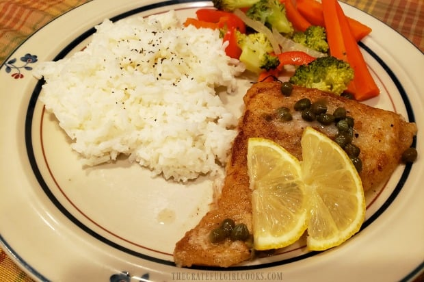 The lemon piccata cod is topped with lemon slices, and served with rice and veggies.