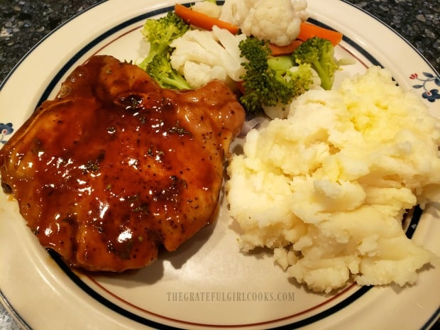 The finished pork chops are served with glaze spooned over the top of each piece.