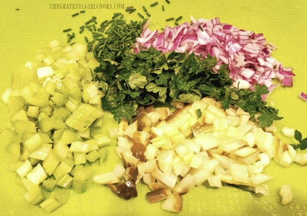 Celery, parsley, red onion, and dill pickles are chopped to add to tuna salad.