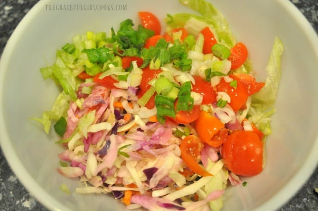 Topping for the baja fish tacos includes cabbage, lettuce, tomatoes, and green onions.
