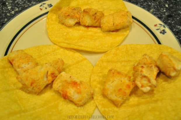 A few pieces of broiled fish are placed in each corn tortilla.