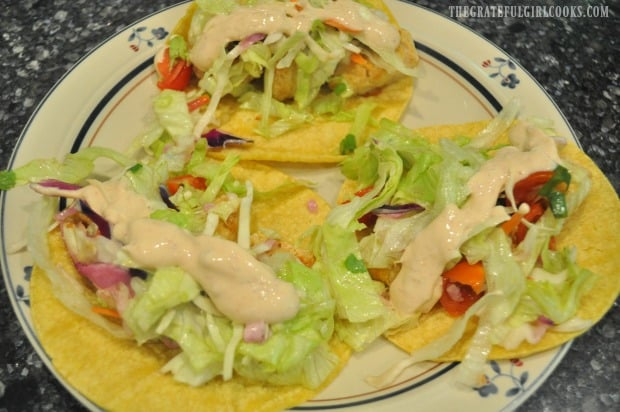 Baja fish tacos are topped with slaw salad and sauce before serving.