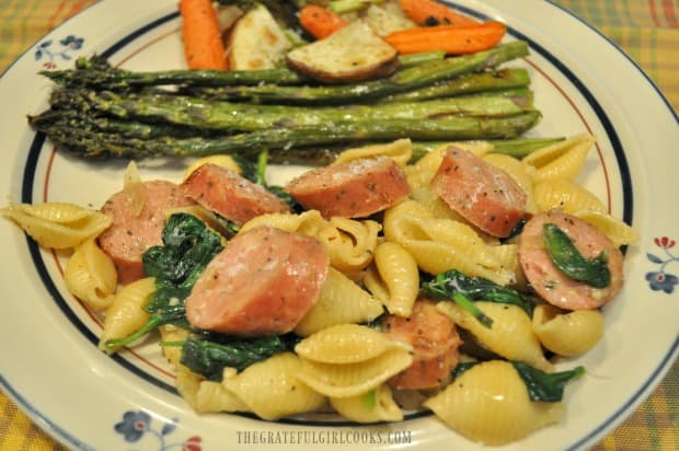 Chicken sausage and spinach pasta, on a plate with roasted veggies.
