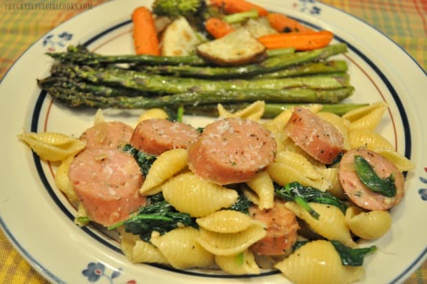Each portion of chicken sausage and spinach pasta is sprinkled with Parmesan cheese.