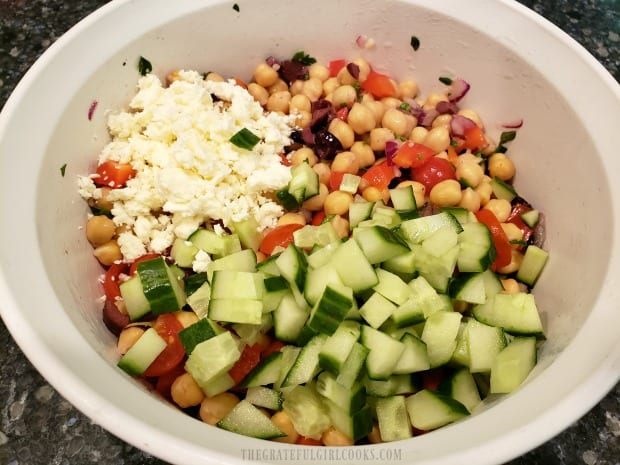 Feta cheese and diced cucumbers are added to the Greek garbanzo salad before serving.