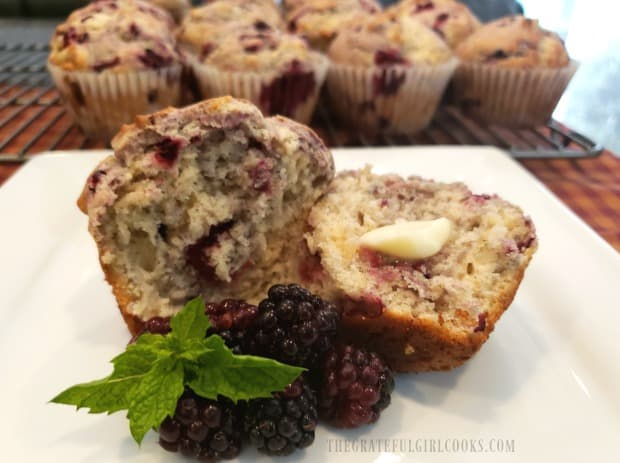 One of the blackberry muffins, cut in half, served with butter.