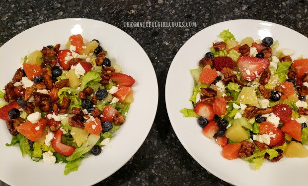 An overhead look at the fruit feta green salad prepared for two people.