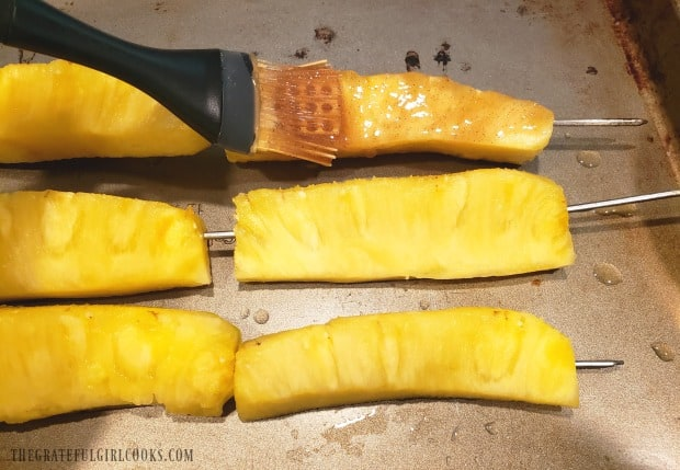 The brown sugar & cinnamon glaze is brushed onto pineapple spears before cooking.