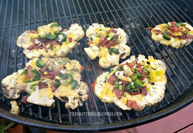 Loaded grilled cauliflower is topped with cheese, bacon, green onions, and jalapeños.