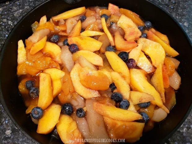 """Fruit for the cobbler is poured into a 9"""" skillet after mixing together."""