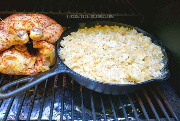 A cast iron skillet full of cobbler is placed onto a Traeger grill, next to roasting chicken.