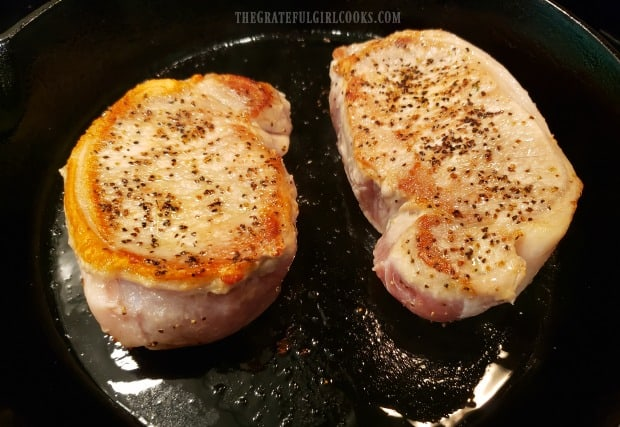 Pork chops are turned to cook other side after turning golden brown.