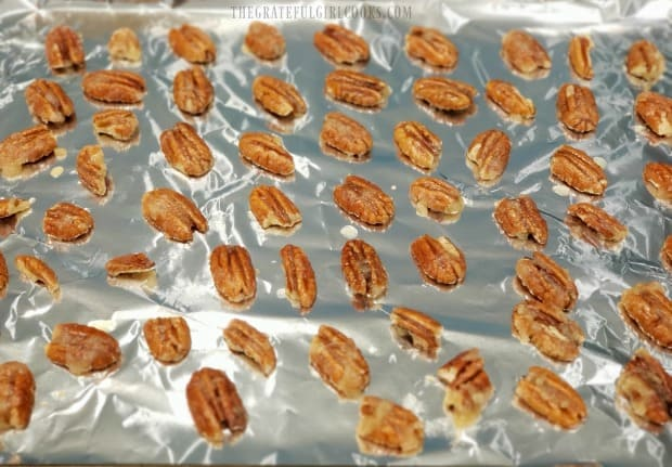 The nuts are laid in a single layer on a foil covered baking sheet prior to cooking.